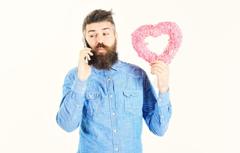 Bearded man holds gift and talks by phone. Talking on phone concept royalty free stock photography