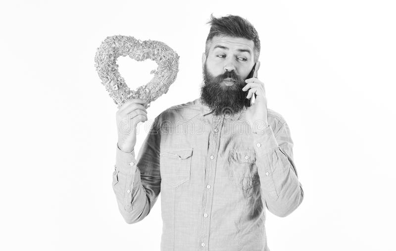 Bearded man holds gift and talks by phone. Talking on phone concept stock image