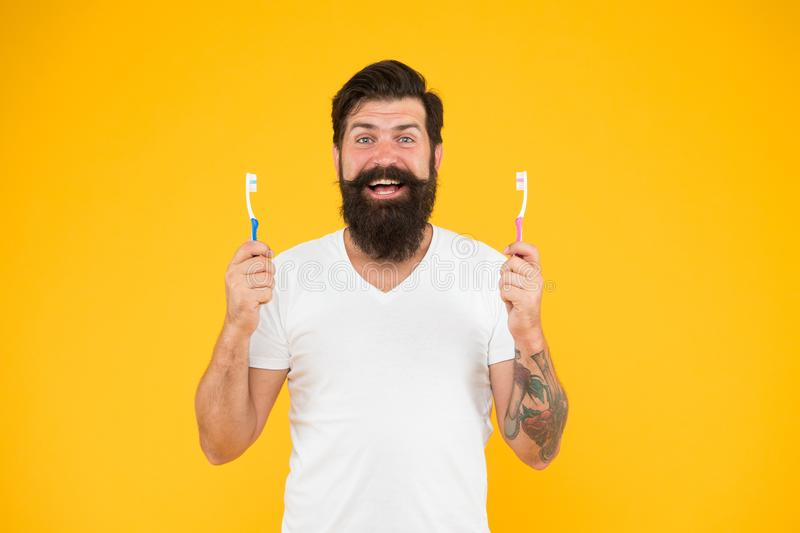 Bearded man holds toothbrushes yellow background. Guy holds two toothbrushes. Hipster happy smiling face cares hygiene stock photo
