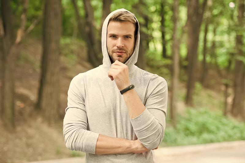Bearded man in hood on natural landscape. Confident sportsman in casual style, fashion. Relax in forest or park. Ready. For workout. Training on fresh air stock images