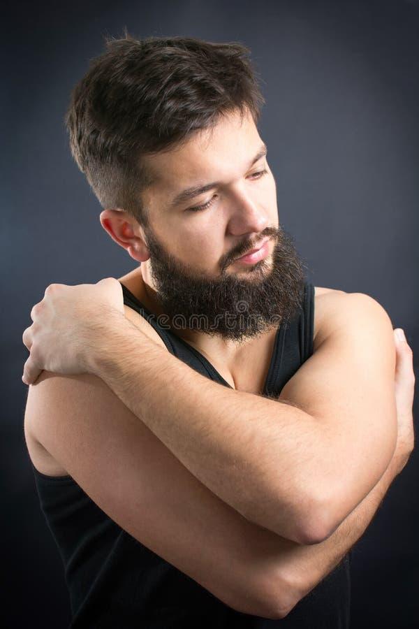Bearded man hugging himself stock image