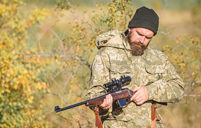Bearded man hunter. Military uniform. Army forces. Camouflage. Hunting skills and weapon equipment. How turn hunting. Into hobby. Man hunter with rifle gun stock photography