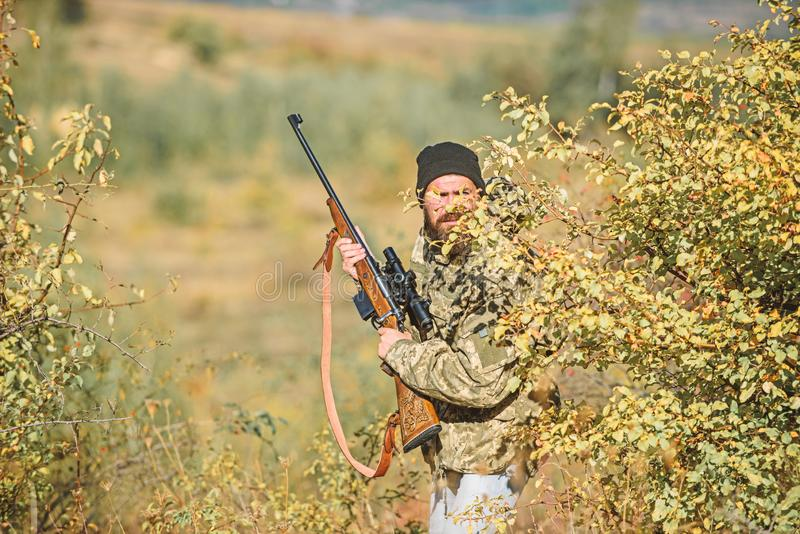 Bearded man hunter. Military uniform fashion. Army forces. Camouflage. Hunting skills and weapon equipment. How turn. Hunting into hobby. Man hunter with rifle royalty free stock images