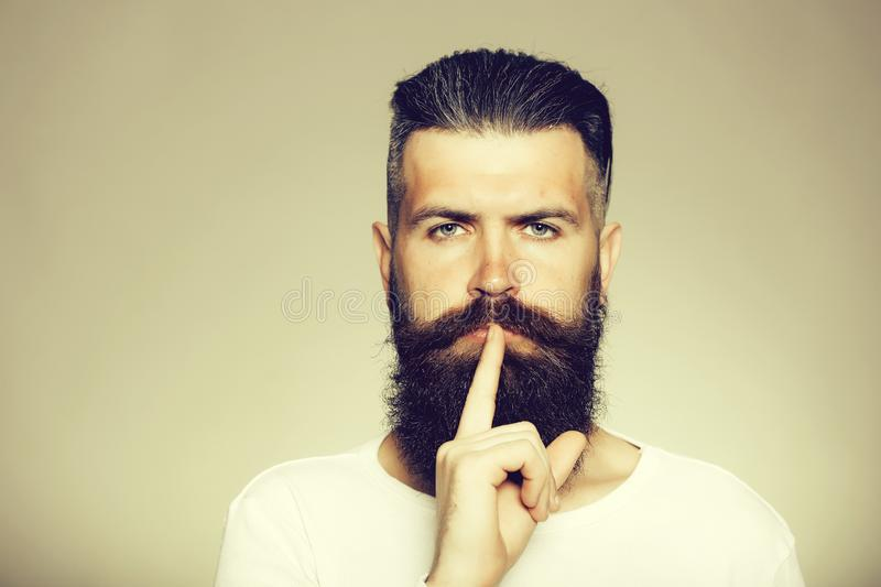 Bearded man with hush gesture royalty free stock photo