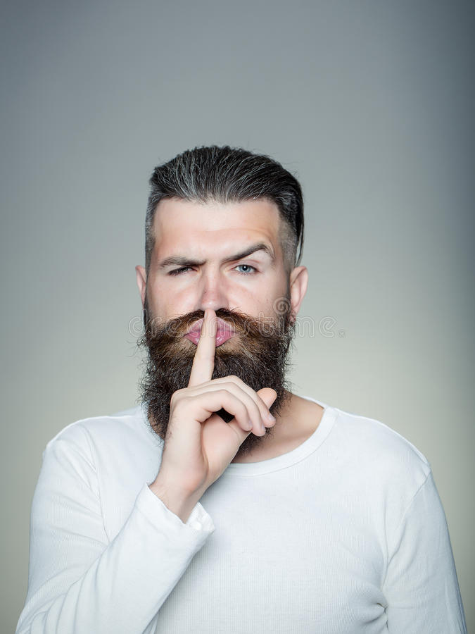 Bearded man with hush gesture stock photography