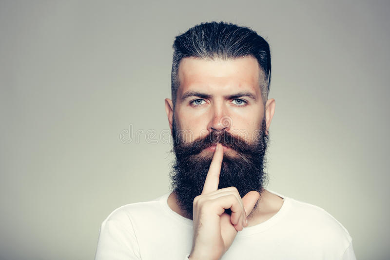 Bearded man with hush gesture royalty free stock photography