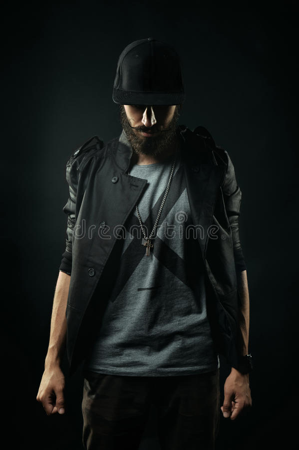 The bearded man in a jacket stands with his head bowed. The brutal bearded man in a black jacket stands with his head bowed stock photos