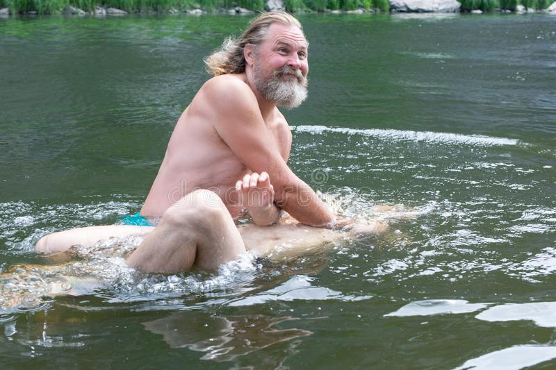 a bearded man dips a man in the water. rite of blessing, baptism. Ceremony Of A Christening outdoor royalty free stock photo