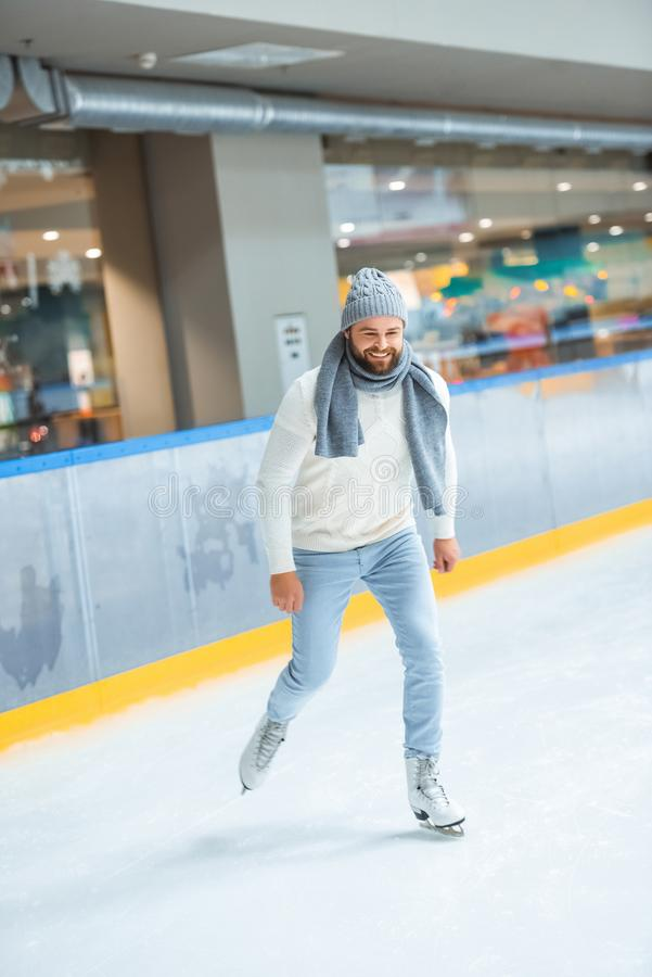 bearded man in knitted hat and sweater skating stock image