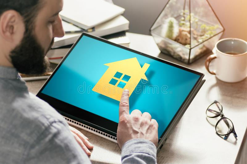 Concept of real estate buying, booking, advertising via internet. Image. Bearded man with laptop at his desk. He presses on the house icon. Concept of real stock photography