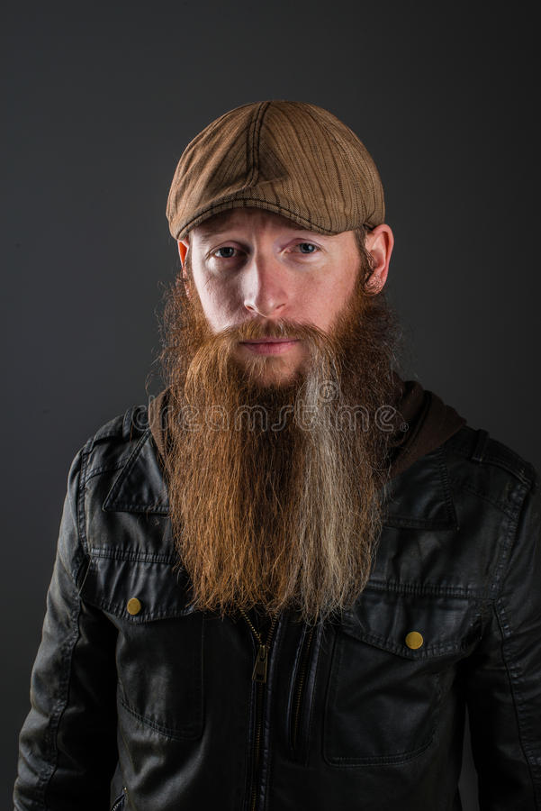 Bearded man with leather jacket and cap. royalty free stock photography