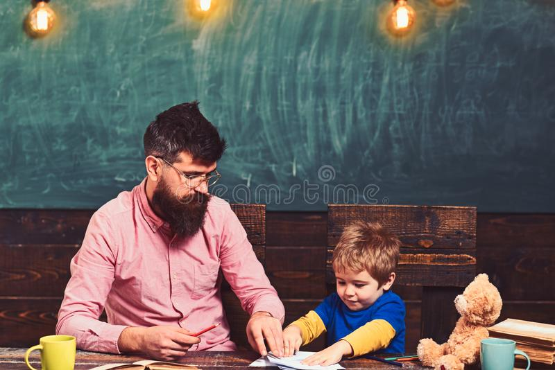 Teacher and little kid sitting at desk with books and teddy bear. Schoolboy playing with copybook. Strict teacher in royalty free stock photo