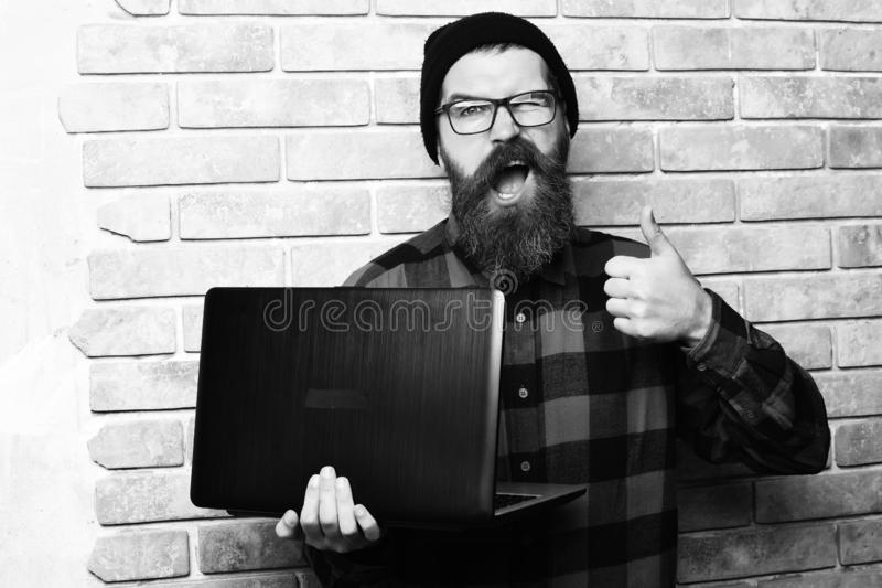 Bearded man, long beard. Brutal caucasian happy unshaven hipster holding laptop in red black checkered shirt with hat. And glasses on beige brick wall studio stock photos