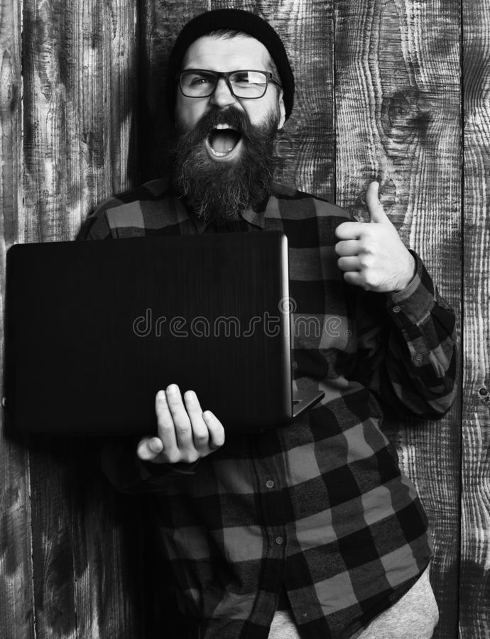 Bearded man, long beard. Brutal caucasian happy unshaven hipster holding laptop in red black checkered shirt with hat. And glasses on brown vintage wooden stock photography