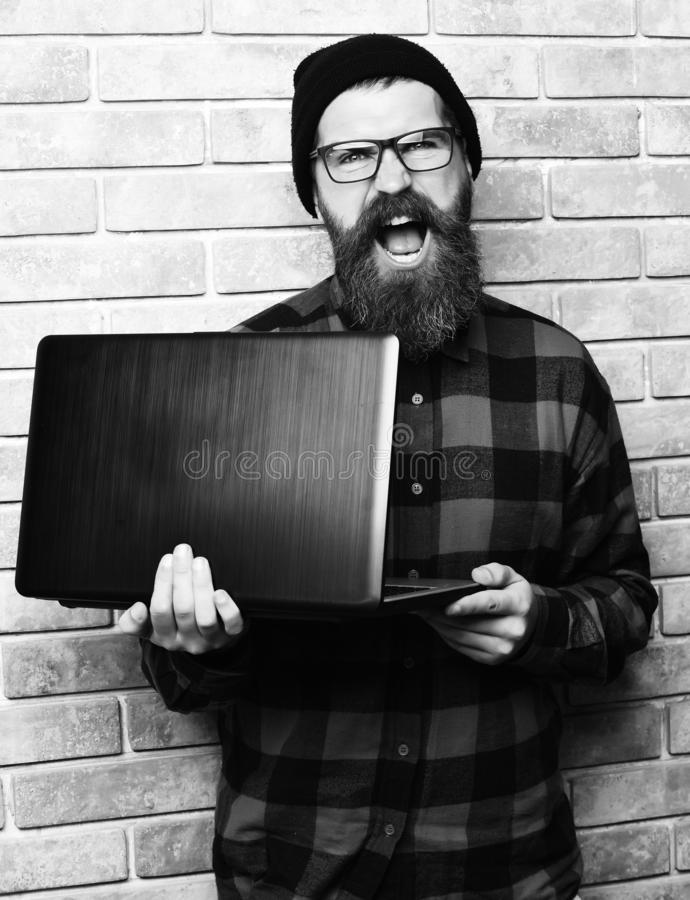 Bearded man, long beard. Brutal caucasian happy unshaven hipster holding laptop in red black checkered shirt with hat. And glasses on beige brick wall studio stock photo
