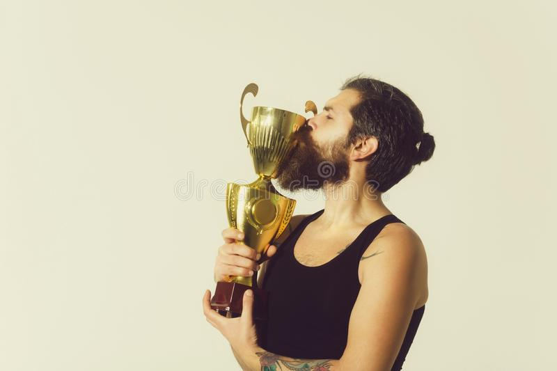 Bearded happy man kissing gold champion cup on grey background. Bearded man, long beard, brutal caucasian hipster with moustache in black vest kissing gold stock photos
