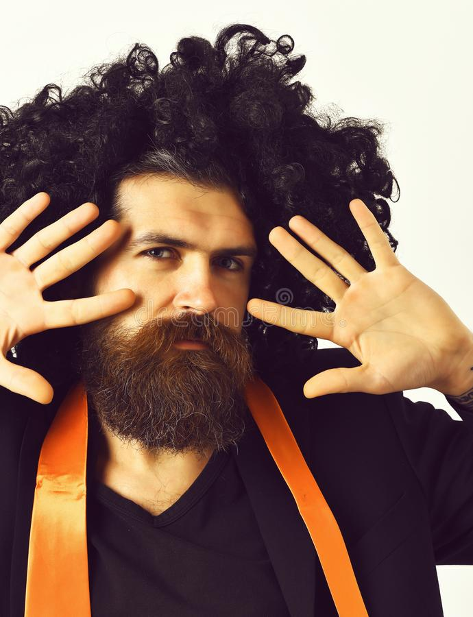 Caucasian hipster in suit and black curly wig stock images