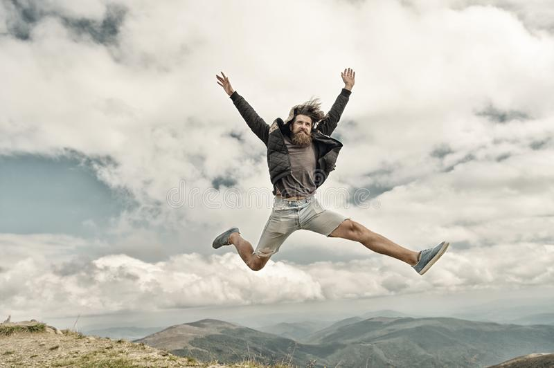 Bearded man, brutal caucasian hipster with moustache jump on mountain royalty free stock images