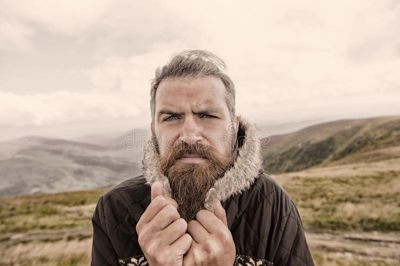 Bearded man, brutal caucasian hipster with moustache cold on mountain. Bearded man, long beard, brutal caucasian hipster with moustache on serious face, unshaven stock images