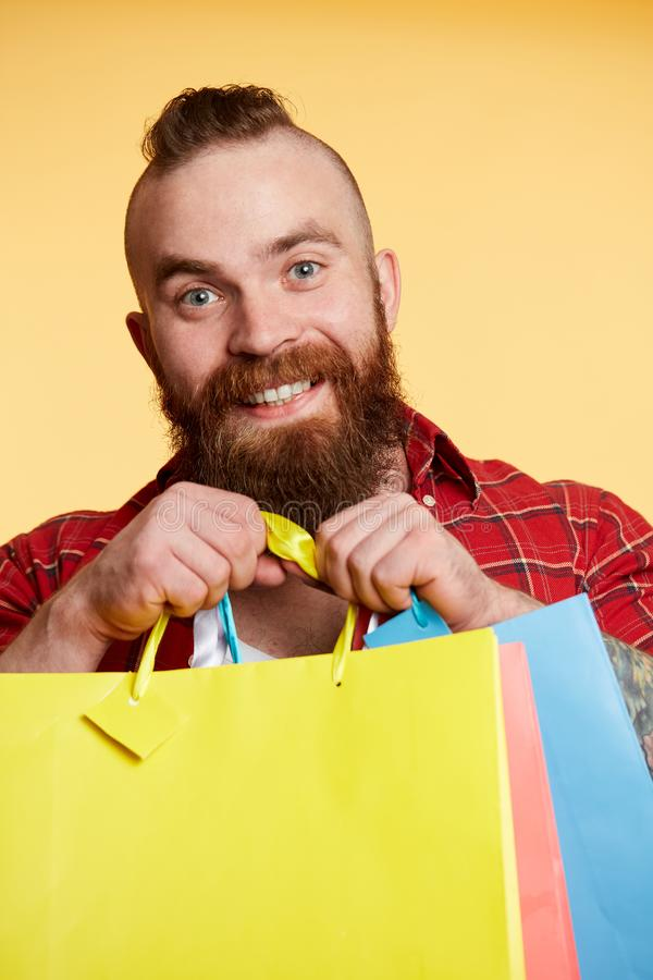 Bearded man, long beard. Brutal caucasian with moustache holding shopping packages. Man, long beard. Brutal caucasian man with moustache holding different color royalty free stock photo