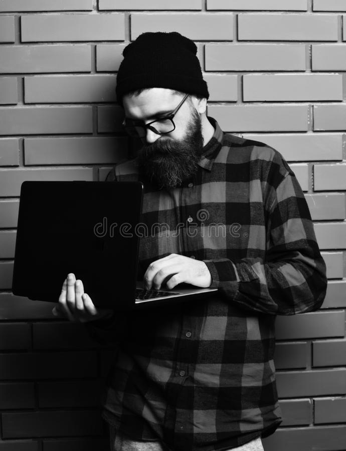 Bearded man, long beard. Brutal caucasian serious unshaven hipster holding laptop in red black checkered shirt with hat. And glasses on brown brick wall studio royalty free stock photography