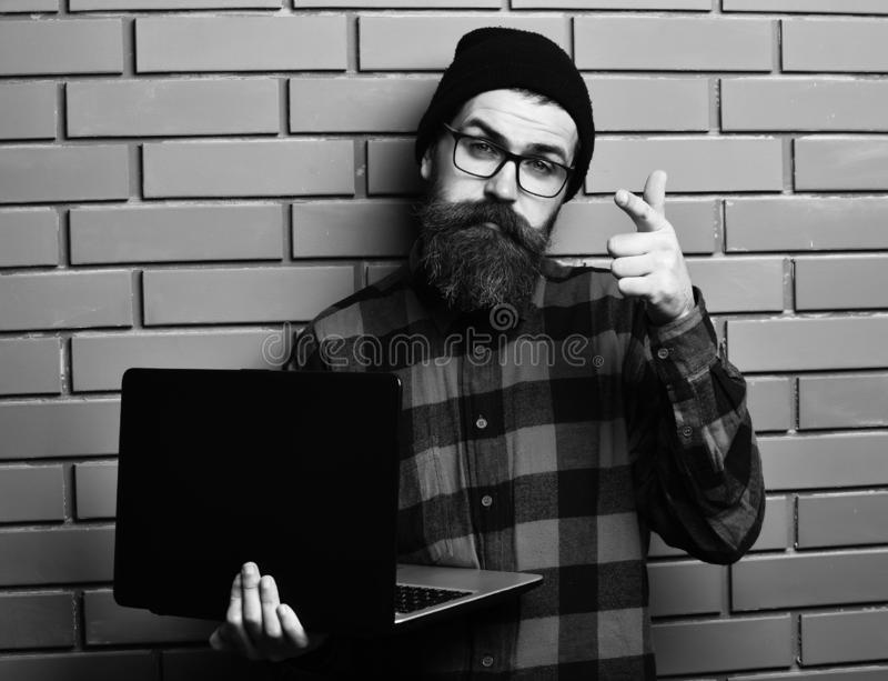 Bearded man, long beard. Brutal caucasian serious unshaven hipster holding laptop in red black checkered shirt with hat. And glasses on brown brick wall studio royalty free stock image