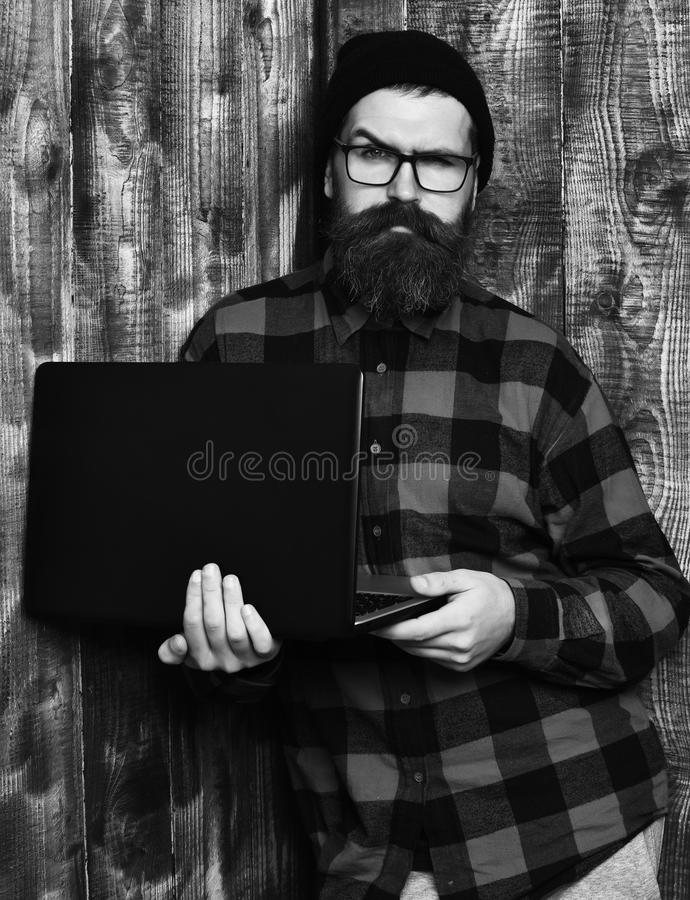 Bearded man, long beard. Brutal caucasian serious unshaven hipster holding laptop in red black checkered shirt with hat. And glasses on brown vintage wooden stock image