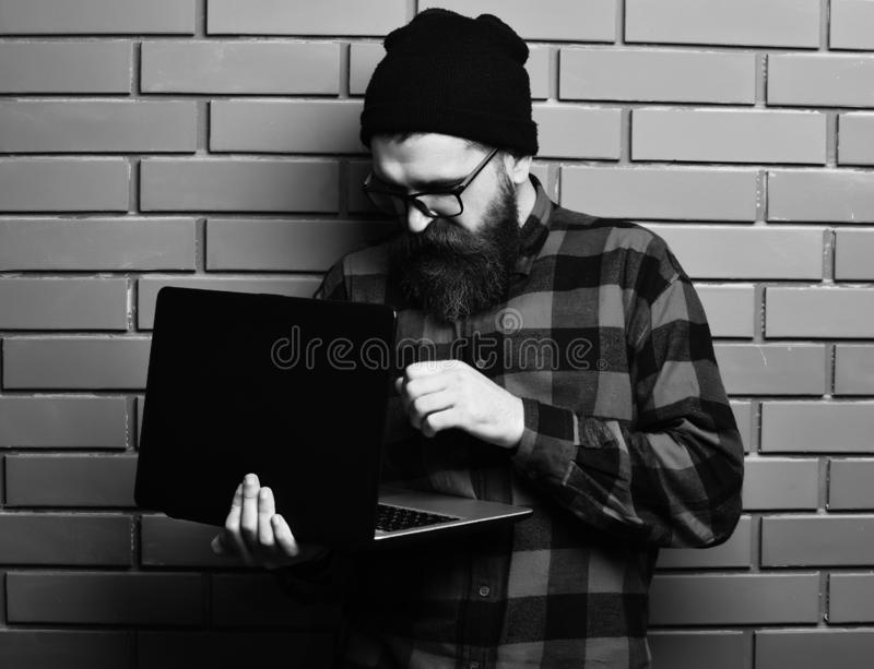 Bearded man, long beard. Brutal caucasian serious unshaven hipster holding laptop in red black checkered shirt with hat. And glasses on brown brick wall studio stock photos