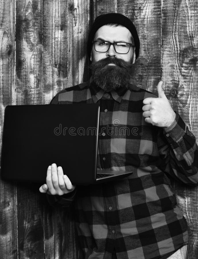 Bearded man, long beard. Brutal caucasian serious unshaven hipster holding laptop in red black checkered shirt with hat. And glasses on brown vintage wooden stock photography
