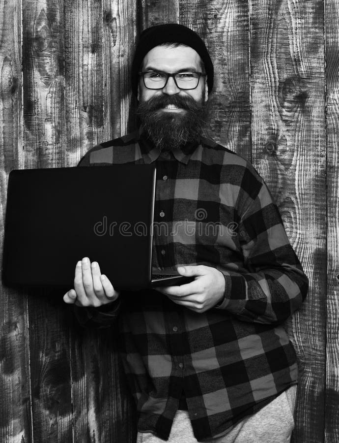 Bearded man, long beard. Brutal caucasian smiling happy unshaven hipster holding laptop in red black checkered shirt. With hat and glasses on brown vintage royalty free stock image