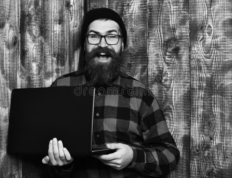 Bearded man, long beard. Brutal caucasian smiling happy unshaven hipster holding laptop in red black checkered shirt. With hat and glasses on brown vintage stock images