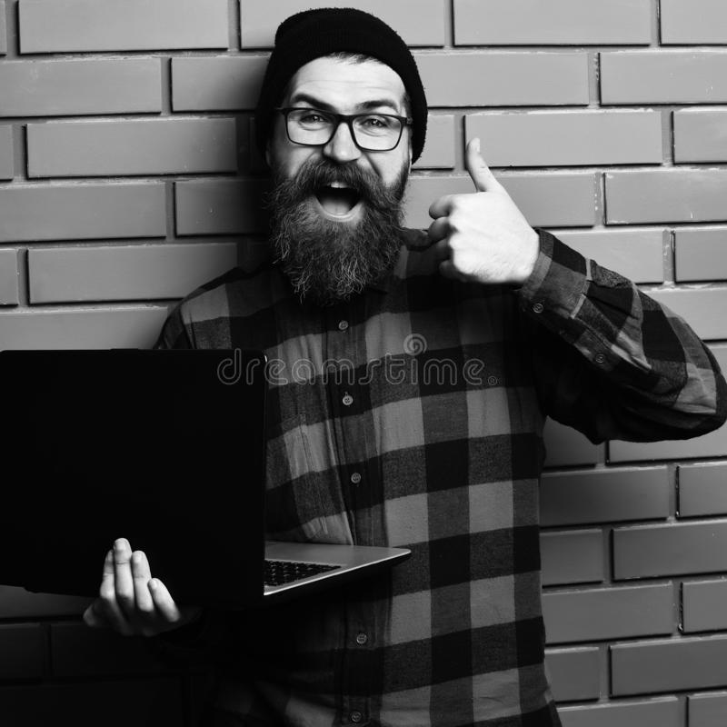 Bearded man, long beard. Brutal caucasian smiling happy unshaven hipster holding laptop in red black checkered shirt. With hat and glasses on brown brick wall stock images