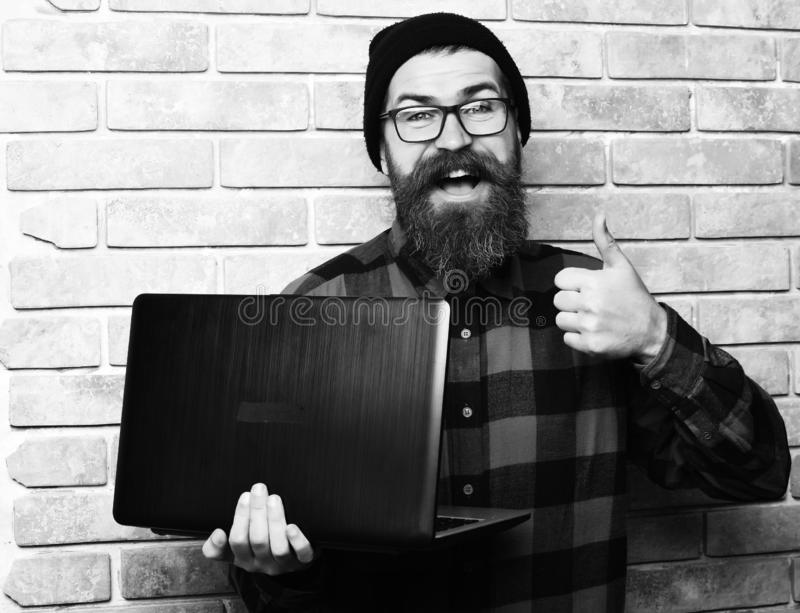 Bearded man, long beard. Brutal caucasian smiling happy unshaven hipster holding laptop in red black checkered shirt. With hat and glasses on beige brick wall stock images