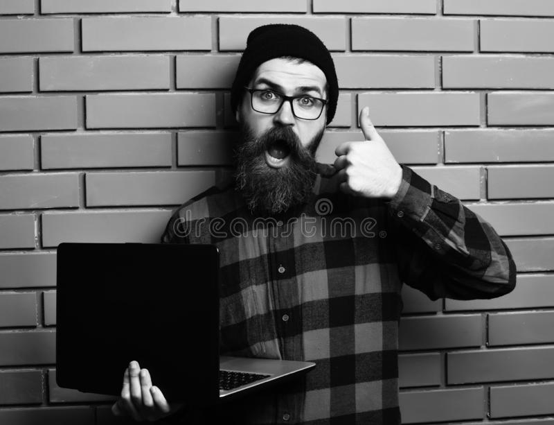 Bearded man, long beard. Brutal caucasian surprised unshaven hipster holding laptop in red black checkered shirt with. Hat and glasses on brown brick wall stock images