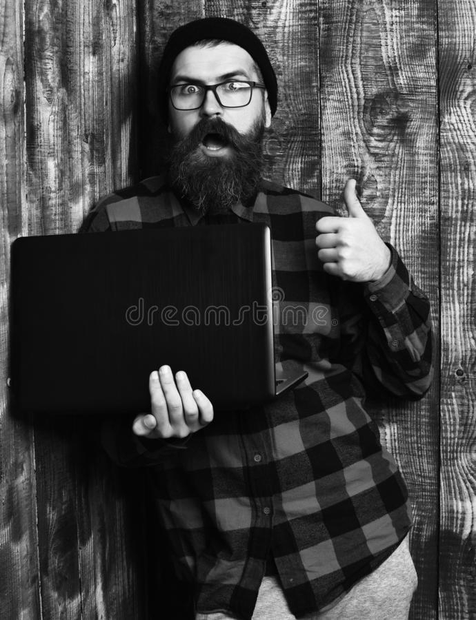 Bearded man, long beard. Brutal caucasian surprised unshaven hipster holding laptop in red black checkered shirt with. Hat and glasses on brown vintage wooden royalty free stock photos