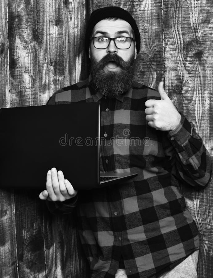Bearded man, long beard. Brutal caucasian surprised unshaven hipster holding laptop in red black checkered shirt with. Hat and glasses on brown vintage wooden stock photo