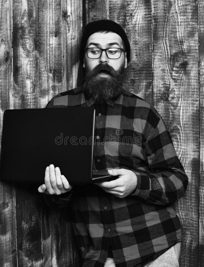 Bearded man, long beard. Brutal caucasian surprised unshaven hipster holding laptop in red black checkered shirt with. Hat and glasses on brown vintage wooden royalty free stock photography