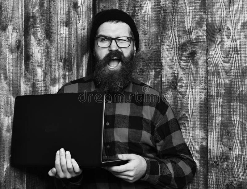 Bearded man, long beard. Brutal caucasian unshaven hipster holding laptop in red black checkered shirt with hat and. Glasses on brown vintage wooden studio royalty free stock photo