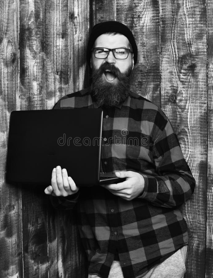 Bearded man, long beard. Brutal caucasian unshaven hipster holding laptop in red black checkered shirt with hat and. Glasses on brown vintage wooden studio royalty free stock photography