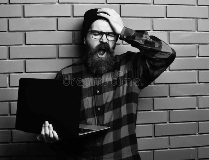 Bearded man, long beard. Brutal caucasian yawning unshaven hipster holding laptop in red black checkered shirt with hat. And glasses on brown brick wall studio royalty free stock image
