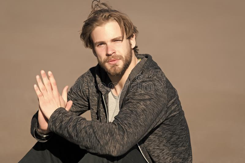 Bearded man with long blond hair outdoor. Macho with beard in casual sportswear on sunny day. Fashion guy with stylish stock photo