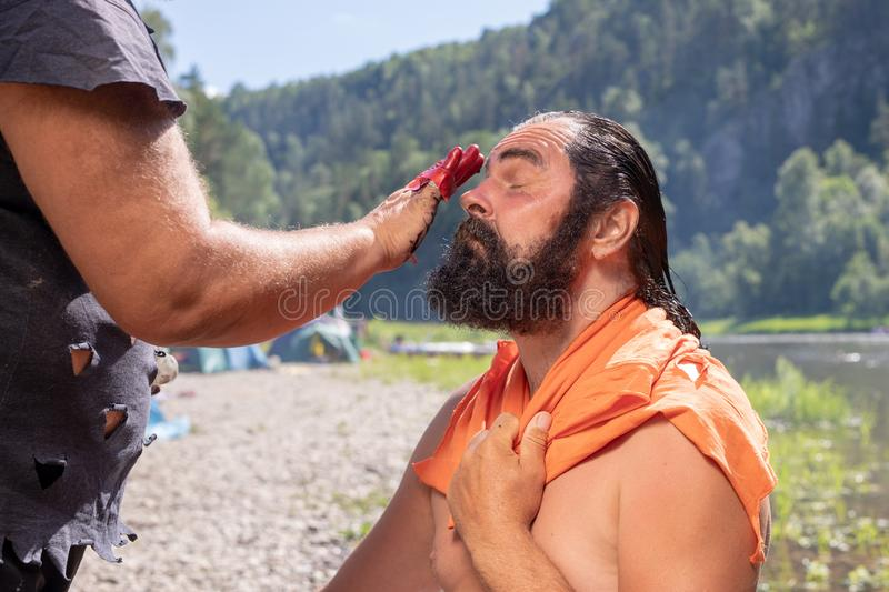 A bearded man with long hair is created a new image, dye his hair and beard. stock photography