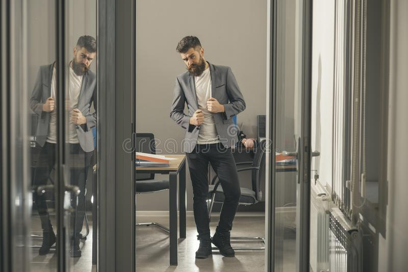 Bearded man look out office door. Bearded man in modern office with glass walls, business lifestyle royalty free stock image