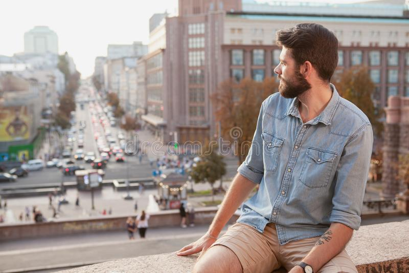 Handsome bearded man enjoying warm day at the city stock photos