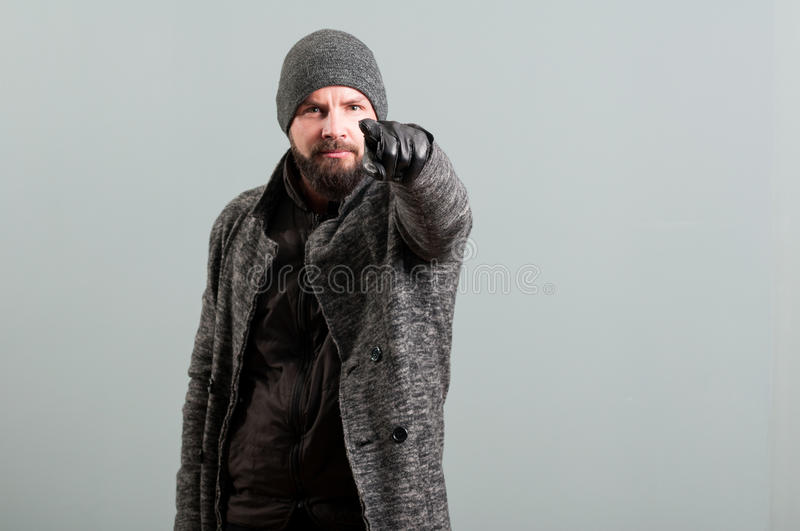 Bearded man looking at camera and pointing finger. On grey background stock photography