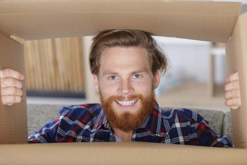 Bearded man looking through cardboard box royalty free stock photography