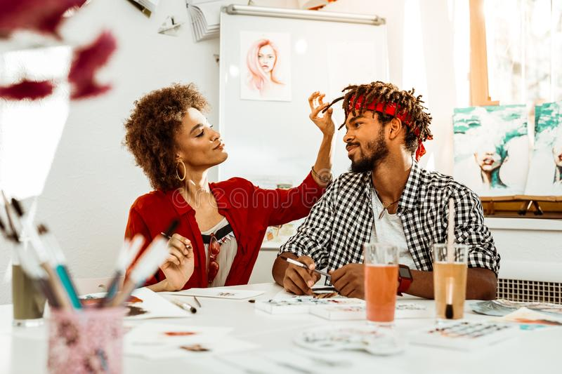 Bearded man looking at his lovely girlfriend touching his dreadlocks. Lovely girlfriend. Caring bearded men looking at his lovely girlfriend touching his royalty free stock photography