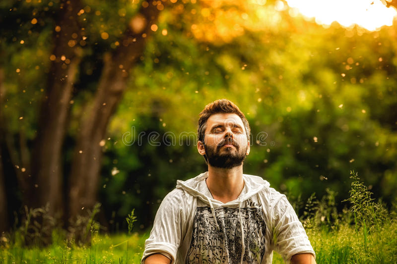 A bearded man is meditating on green grass in the park. With face raised up to sky and eyes closed on sunny summer day. Concept of meditation, dreaming royalty free stock images