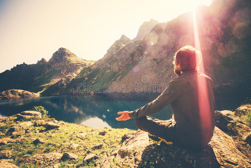 Bearded Man meditating yoga relaxing alone sitting lotus pose on stone Travel healthy Lifestyle. Concept lake and mountains sunny landscape on background stock image