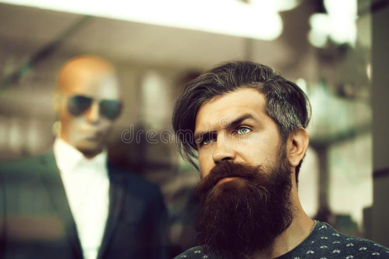 Bearded man near showcase with dummy stock photos